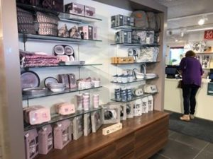 Hylle med barneytstyr. Bilde av lokalene til butikken Alt p책 stell. Matboks, sekk, kopp.