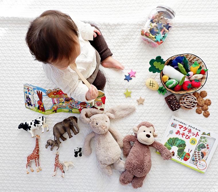 et barn sittende på teppe med leker og bamser