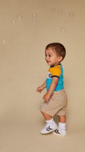 Liten gutt med hummel t-skjorte, shorts og sko